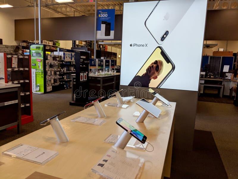 IPhone X de Apple e iPad com o assistente do siri na exposição dentro de Best Buy fotos de stock