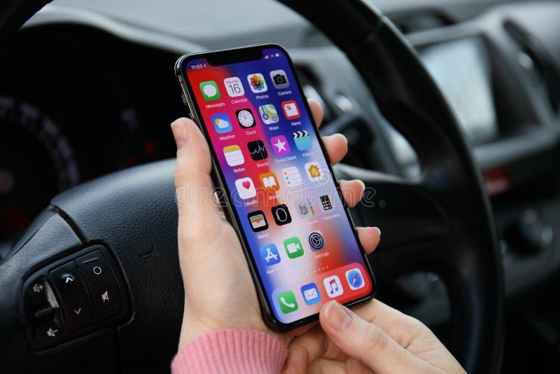 IPhone X della tenuta della mano della donna con l'IOS 11 in automobile immagini stock
