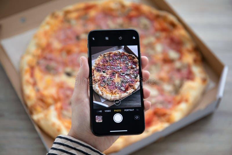 IPhone X della tenuta della mano della donna con la consegna della pizza della foto fotografia stock
