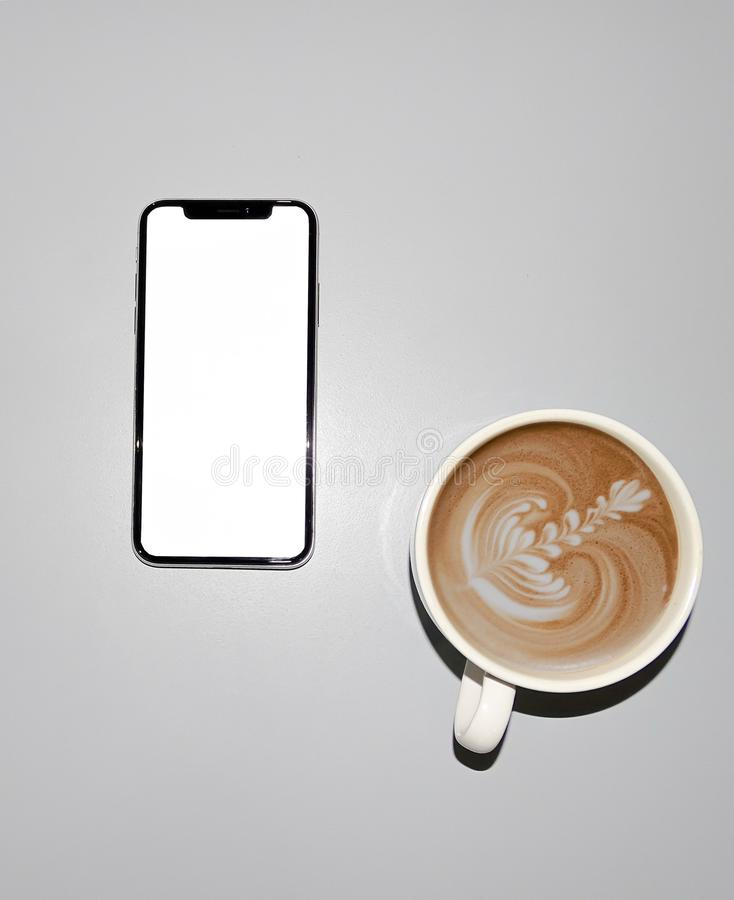 IPhone X en een kop van koffie stock foto