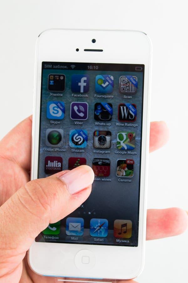 IPhone 5 i en hand som isoleras på vit fotografering för bildbyråer