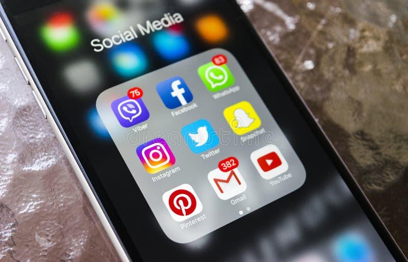 Iphone 6 más con los iconos de medios sociales en la pantalla en la tabla de cristal Smartphone del estilo de vida de Smartphone  fotos de archivo libres de regalías