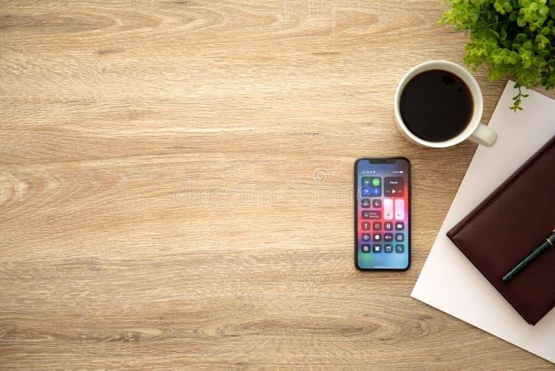IPhone X mit hölzernem Schreibtisch Hauptschirm Control Center-Hintergrundes stockfoto