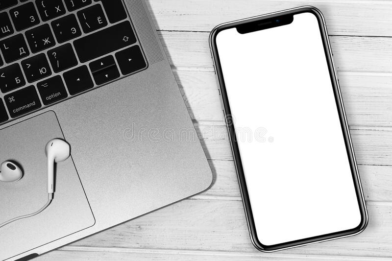 IPhone mockup and Apple Macbook with Earpods closeup at the white office desk. Blank screen mobile phone for graphic display montage. Moscow, Russia - December stock photo