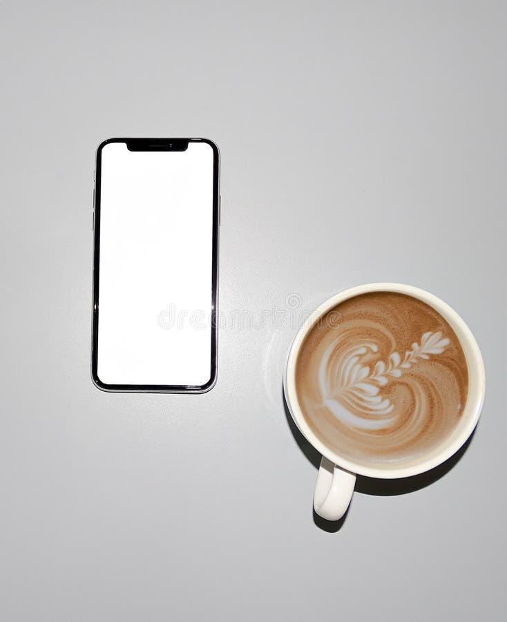 IPhone X och en kopp kaffe arkivfoto