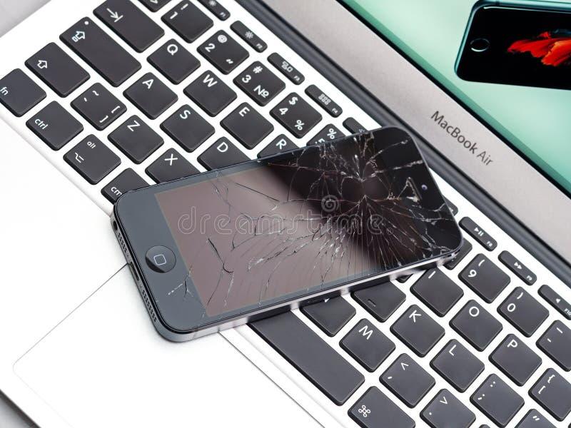IPhone quebrado de Apple no portátil do ar de Apple MacBook fotos de stock