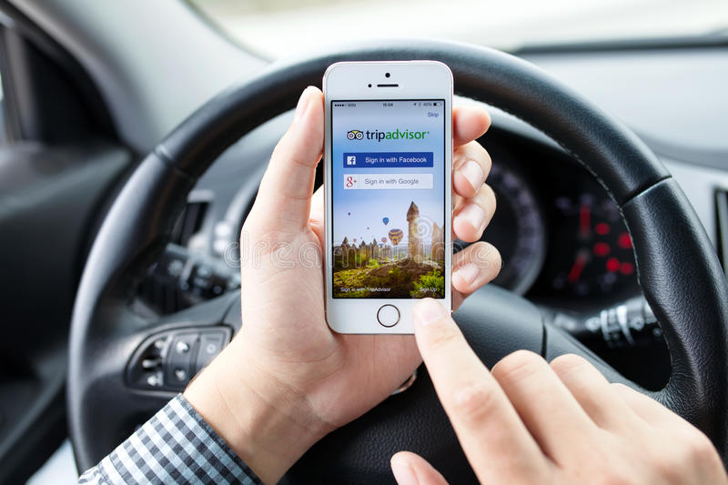 IPhone 5S app TripAdvisor in hands of the driver car. Simferopol, Russia - September 22, 2014: TripAdvisor tourist community in which it is possible to receive