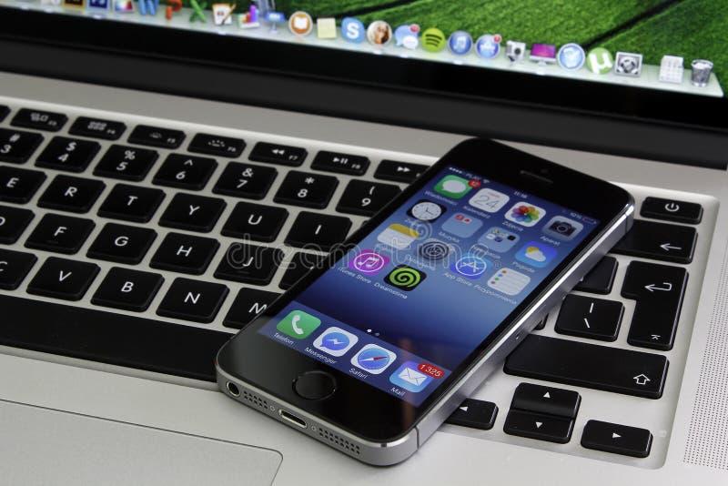 IPhone 5s que miente en teclado del macbook de la retina el favorable fotos de archivo libres de regalías