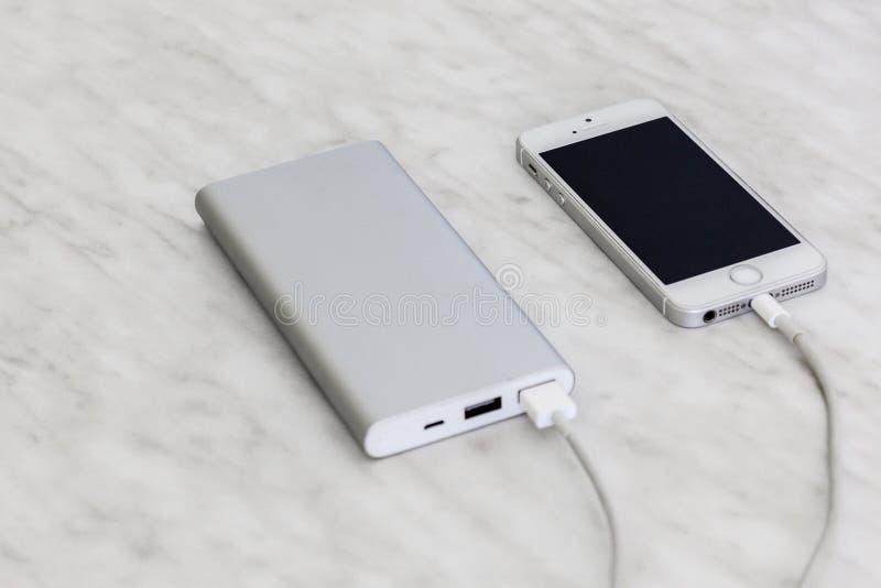 IPhone SE ładuje z władza bankiem na marmurowym tle zdjęcia royalty free