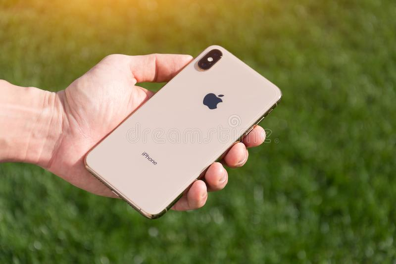 IPhone Xs Max gold smartphone model by Apple Computers close up in male hand on the background of green grass. Italy royalty free stock image