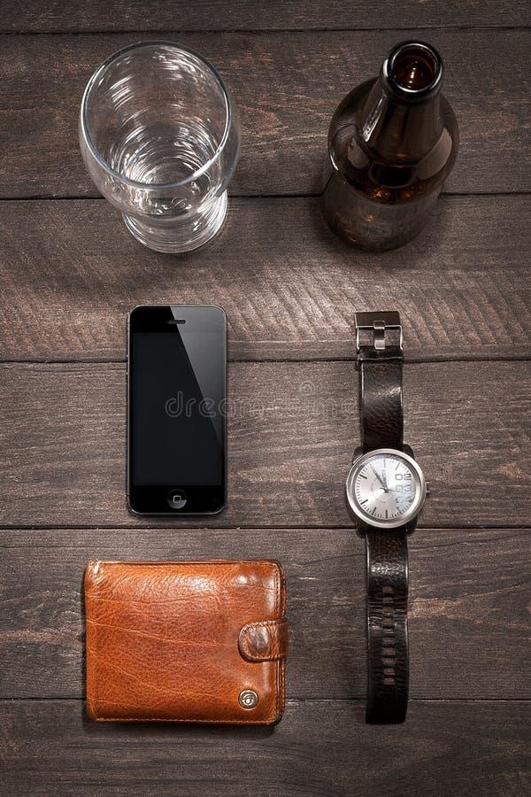 Iphone y de la cerveza de los relojes cerca en de madera foto de archivo libre de regalías