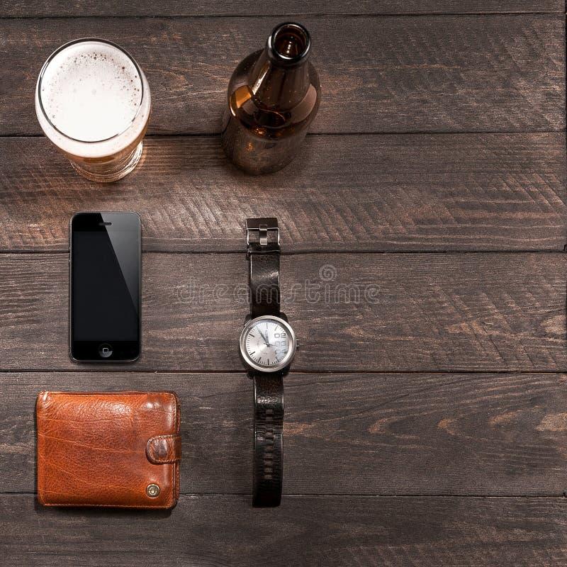 Iphone y vidrio de la cerveza de relojes cerca en de madera fotografía de archivo