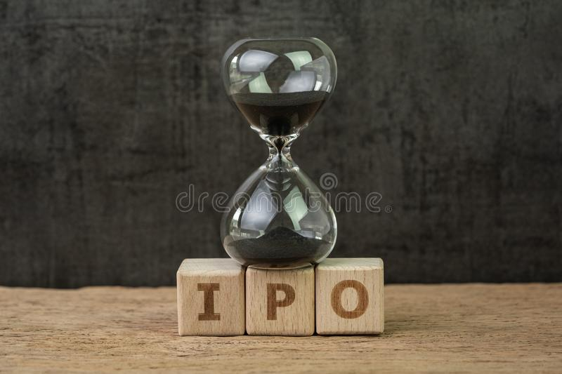 IPO, Initial Public Offering for company to buy and sell in stock market, sandglass or hourglass on wooden cube block with. Alphabet building the word IPO on royalty free stock photo