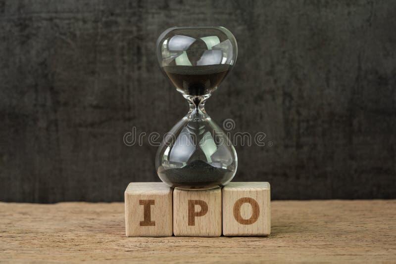 IPO, oferta pública inicial para que compañía compre y venda en existencia el mercado, sandglass o el reloj de arena en bloque de foto de archivo libre de regalías