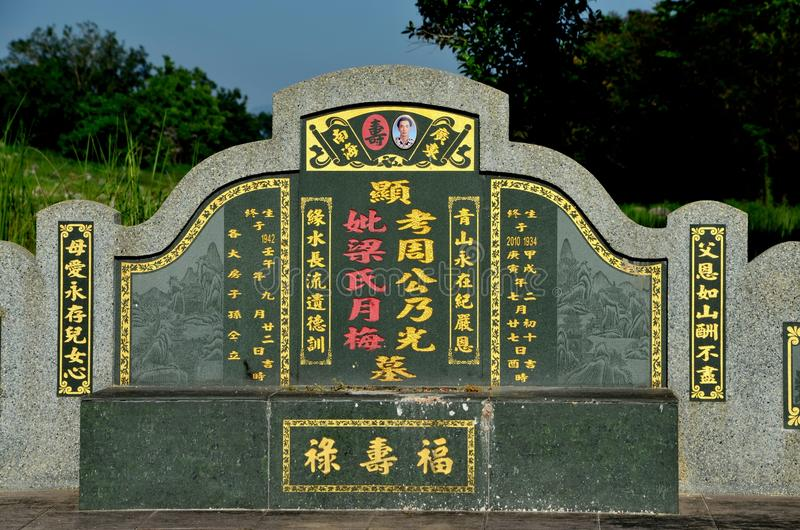 Large Chinese grave and tombstone with golden Mandarin writing at cemetery Ipoh Malaysia. Ipoh, Malaysia - June 3, 2017: A large, traditional Chinese grave of a royalty free stock photo