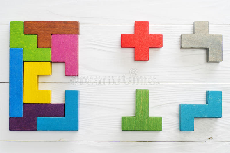 IQ test. Choose correct answer. Logical tasks composed of colorful wooden shapes, top view. Children`s educational logical task, flat lay. Visual conundrum royalty free stock photo