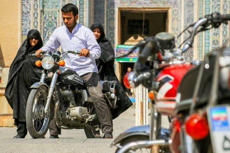 Irã, Pérsia, Yazd - em setembro de 2016: Povos locais perto da mesquita nas ruas da cidade velha Foto da rua fotografia de stock