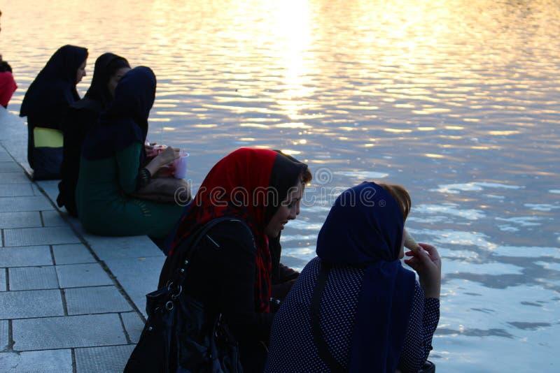 Irańskie kobiety wzdłuż Zayanderud rzeki przy zmierzchem w Isfahan, Iran obraz royalty free