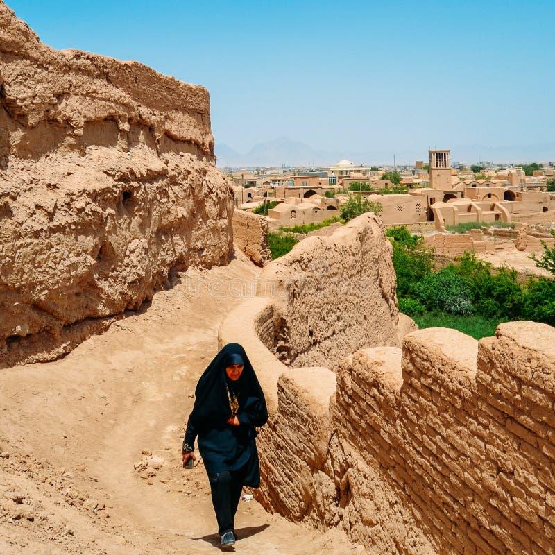 Irańska kobieta jest ubranym tradycyjną suknię, znać jako chador, chodzi w górę wzgórza z miastem Yazd w tle fotografia royalty free