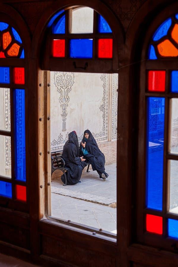 Irańskie kobiety na ławki inTabatabaei dziejowym domu, Kashan, Ir zdjęcie stock