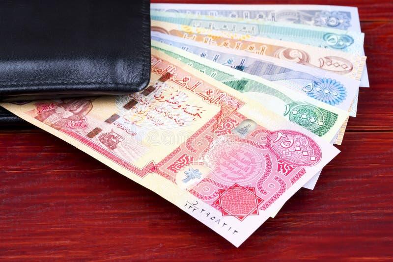 Iraakse Dinar in de zwarte portefeuille stock foto