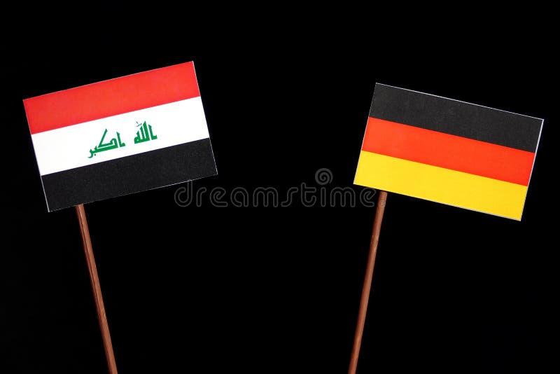 Irakische Flagge mit deutscher Flagge auf Schwarzem lizenzfreie stockfotografie