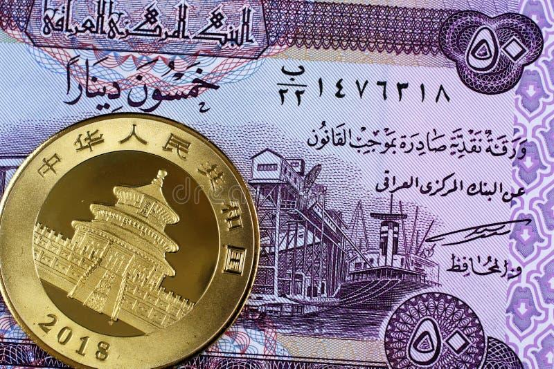 Irakisk 50 dinar anmärkning med ett kinesiskt guld- mynt arkivfoto