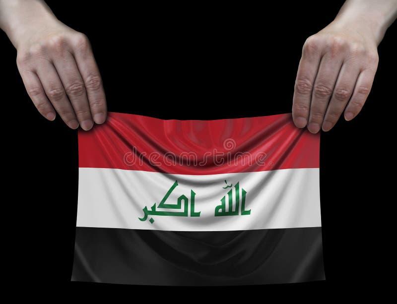Irakisk flagga i händer arkivbilder