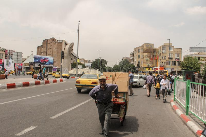 Tabriz, Iran - 10 July 2017: Street of Iran with a  carrier in the middle of the road with cars around. Guy delivering cardbox in royalty free stock photo