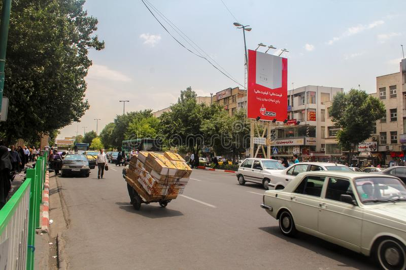 Tabriz, Iran - 10 July 2017: Street of Iran with a  carrier in the middle of the road with cars around. Guy delivering cardbox in royalty free stock photos