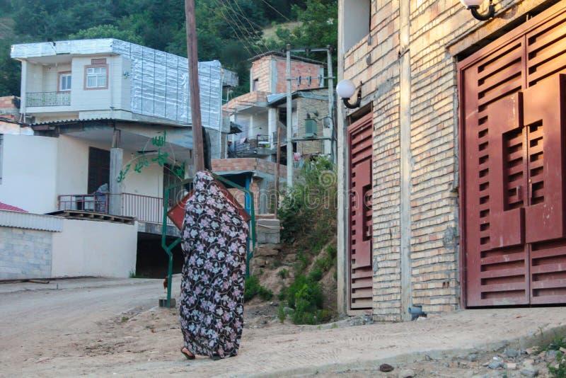 Mazandaran, Iran - 19 July 2017: Iranian woman with traditional colourful burka in a rural area of Iran walking in the village stock image