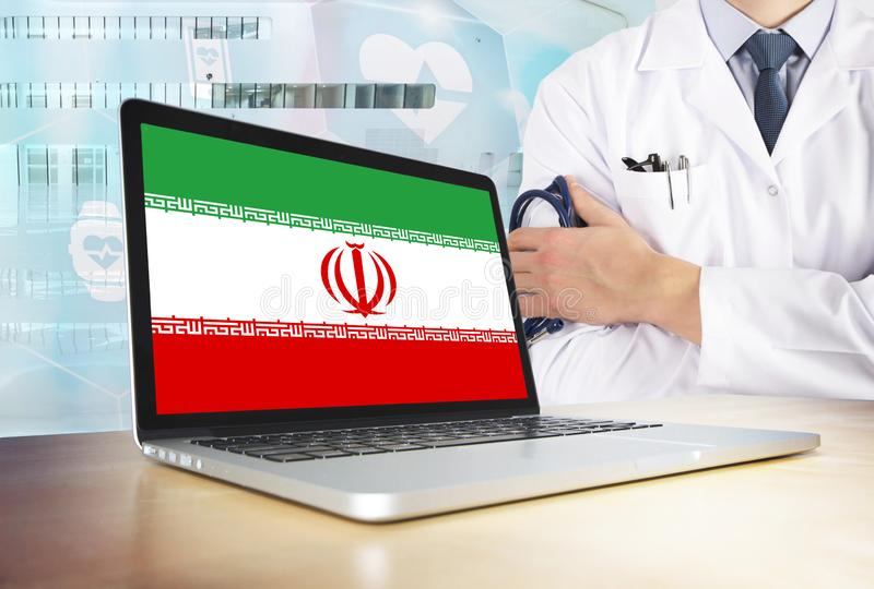 Iran healthcare system in tech theme. Iranian flag on computer screen. Doctor standing with stethoscope in hospital. Cryptocurrency and Blockchain concept stock photos