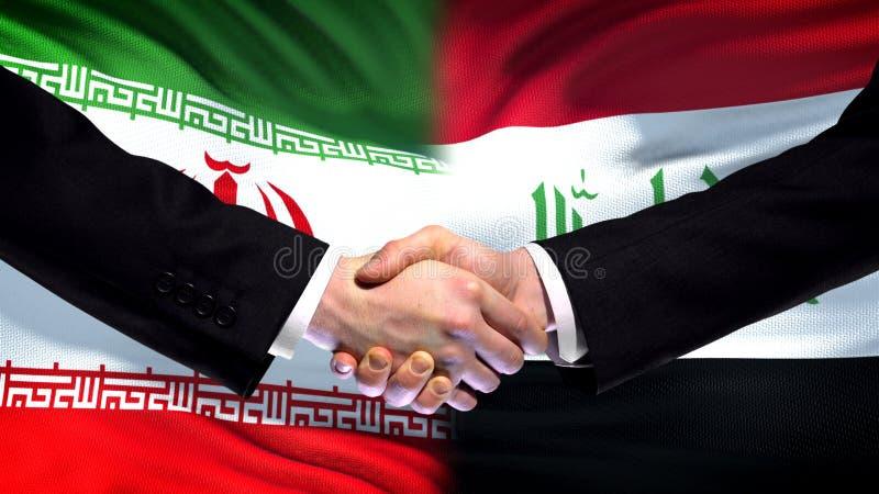 Iran och Irak handskakning, internationell kamratskapförbindelse, flaggabakgrund arkivfoton
