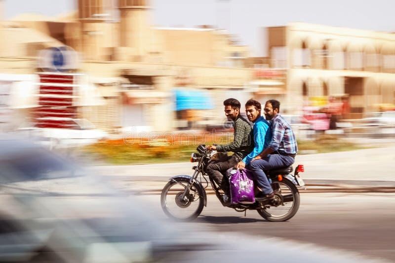 Iran, Perzië, Yazd - September 2016: drie kerels die bij hoge snelheid op een motorfiets op het achtergrondmotieonduidelijke beel stock foto's