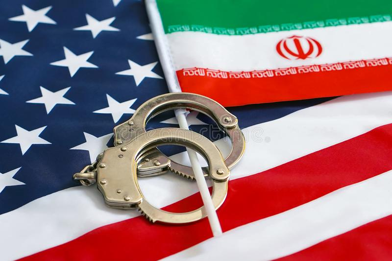 Flag of USA and Iran. Handcuffs. Sanctions royalty free stock photo