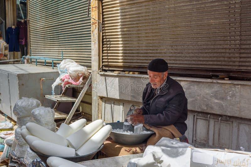 Iranian man crashing sugar cones for sale in bazaar. Sanandaj. Kurdistan Province. Iran stock photos