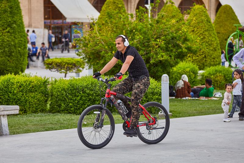 Iranian man with headphones rides bicycle in park, Isfahan, Iran royalty free stock image