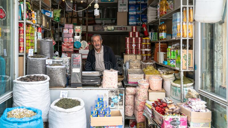 Iranian man selling snacks in his shop in Grand Bazaar of Isfahan, Iran royalty free stock photo