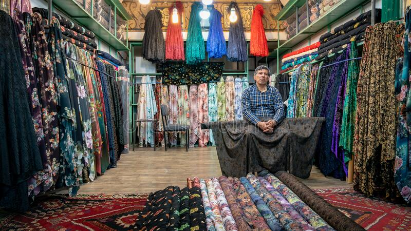 Iranian man selling textiles in in his small shop in Grand Bazaar of Isfahan, Iran stock images
