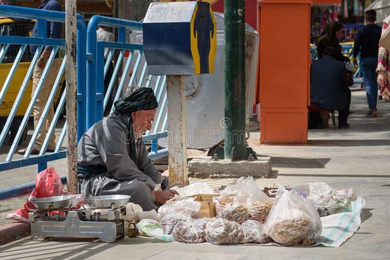 Iranian man sells nuts on the street near bazaar in Sanandaj. Iran stock photos