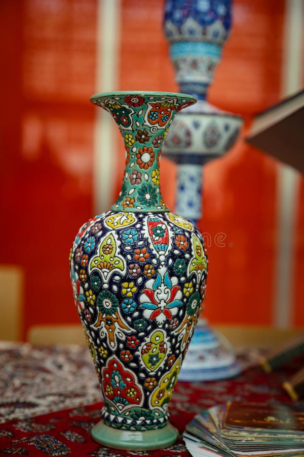 Iranian porcelain vase with national handmade ornament.On a silk handkerchief against a high vase and an orange tulle curtain. royalty free stock photos