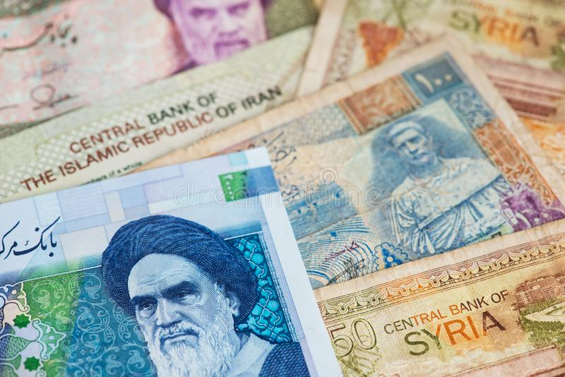 Iranian Rial and Syrian Pounds banknotes close up image.. Iranian Rial and Syrian Pounds banknotes close up image. Iranian Rial and Syrian Pounds money. US royalty free stock photo