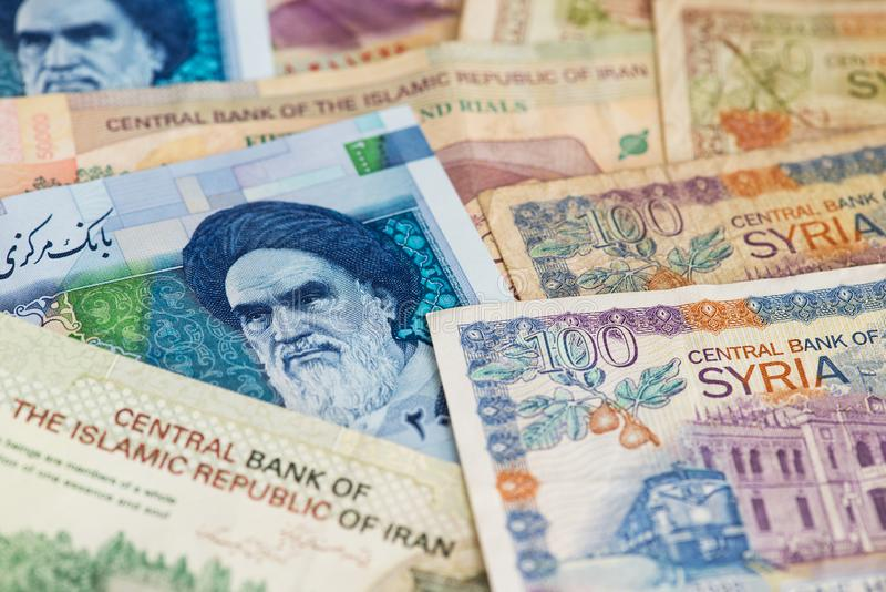 Iranian Rial and Syrian Pounds currency banknotes. Iranian Rial and Syrian Pounds banknotes. Iranian Rial and Syrian Pounds money. US sanctions on Iran oil royalty free stock photography