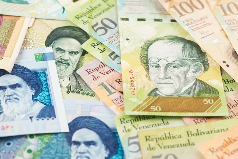Iranian Rial and Venezuelan Bolivar hyperinflation banknotes. Venezuela Iran Bolivar Rial Hyperinflation Money US Sanctions Oil Gas royalty free stock photography