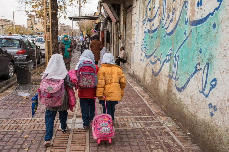 Iranian schoolgirls walk on the streets of Shiraz city, Iran. Shiraz, Iran - December 26, 2015: Iranian schoolgirls walk on the streets of Shiraz city, Iran stock images