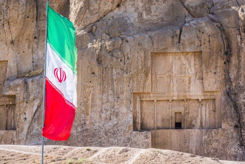 Iransk flagga med den forntida nekropolen Naqsh-e Rustam i det Fars landskapet, Iran i bakgrund arkivfoton