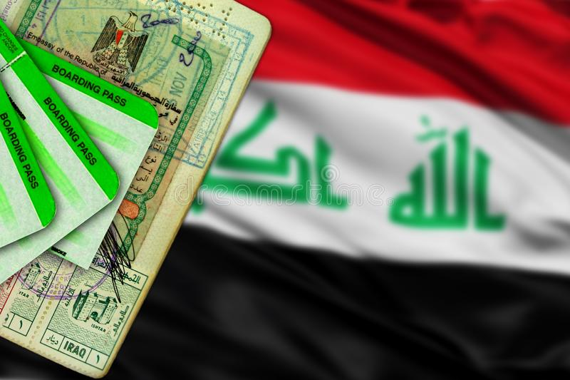 Iraq visa in passport and boarding passes. Close up of document issued by Embassy during Saddam Hussein regime. Blurred Iraqi flag stock images