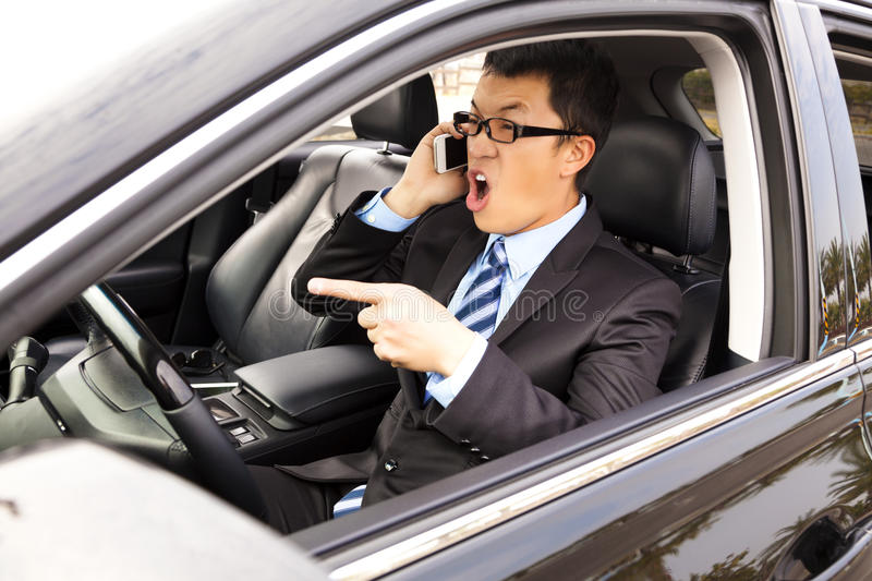 Irate businessman talking with cell phone. Irate asian businessman talking with cell phone in the car stock image
