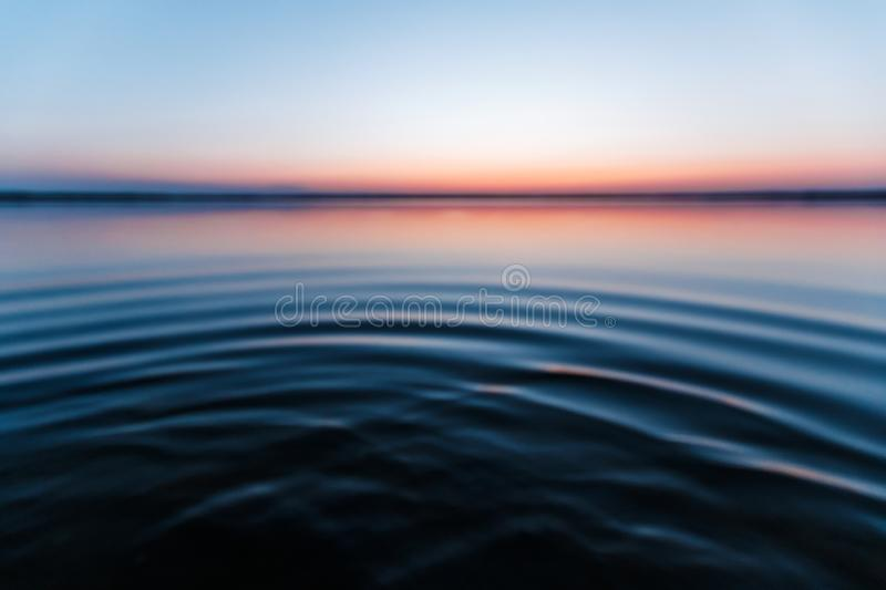 Ircles on the water against a beautiful, pink sunset. The magic time of day royalty free stock photos