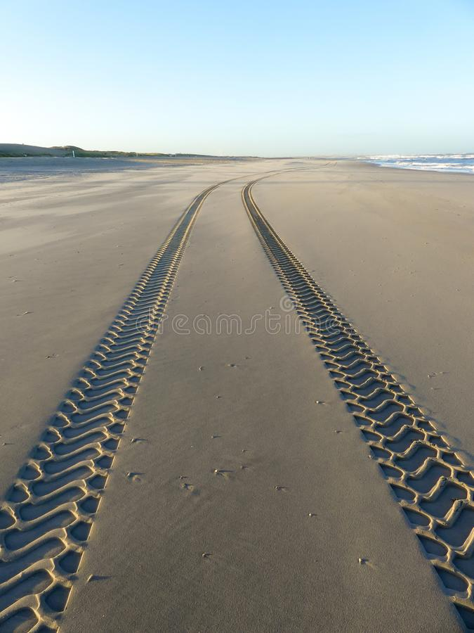 Ire tracks on smooth sandy deserted beach. Tire tracks on smooth sandy deserted beach on sunny day with blue sky royalty free stock photo